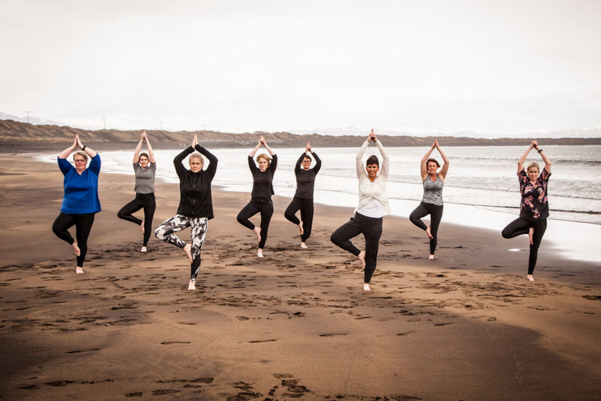 A group on women does a yoga pose on the black beach in Þorlákshöfn