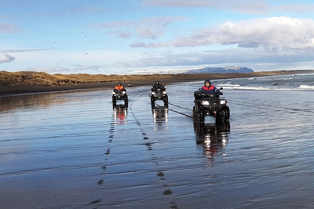 Three buggies driving on the black beach